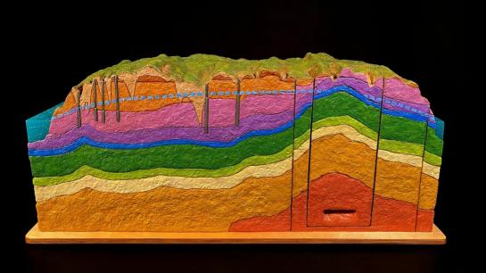 A cross section of colored layers representing geological layers