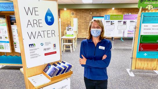 """A woman in a blue shirt wearing a face mask stands next to a large sign that says """"We Are Water"""". Other exhibits are around her."""