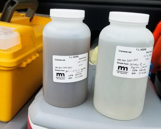 Two white plastic jars with water samples. The water in the jar on the left is a dark color, the water in the jar on the right is a light color.