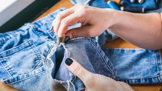 two hands mending a pair of ripped jeans