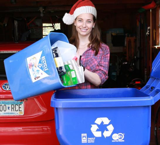 Woman in Santa hat putting recyclables into recycling bins