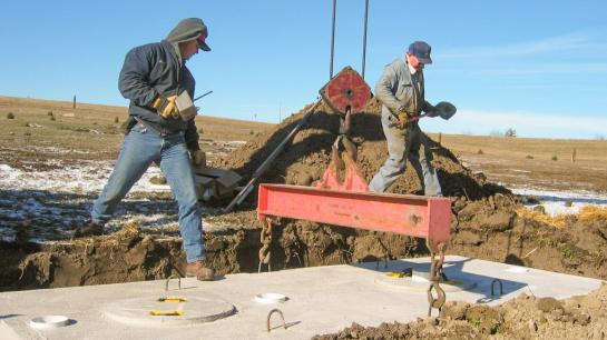 A man steps onto the top of a concrete septic system that has just been lowered into the ground.