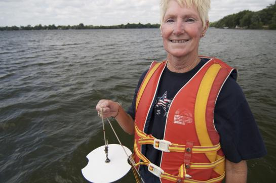 Woman with white hair wearing orange life jacket standing by lake holding white secchi disk by the string