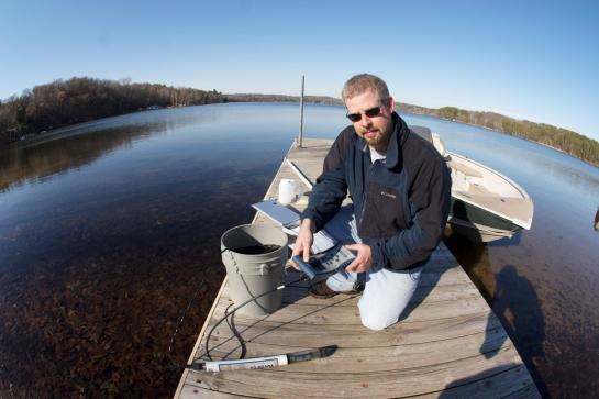 Man kneeling on dock with bucket and other water monitoring equipment