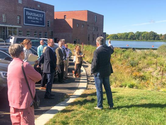 A man speaking to a group of people outside a brick building. The man is gesturing toward a rain garden and river in the distance.