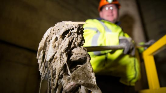 Worker shows pile of flushed wipes raked from a grate in a lift station
