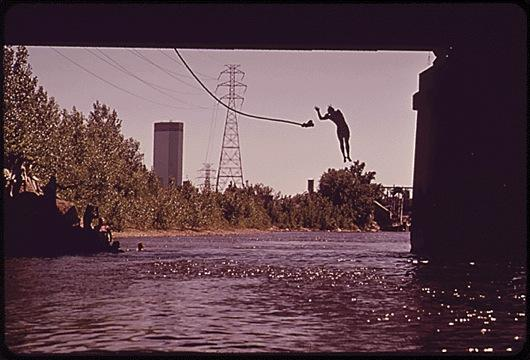 person swinging on a rope and swimming under a bridge near downtown minneapolis
