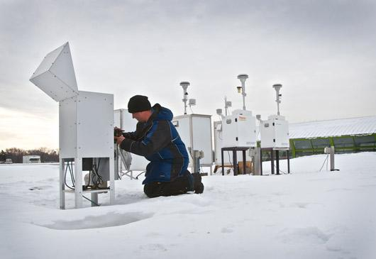 MPCA air tech checking monitoring equipment in snow