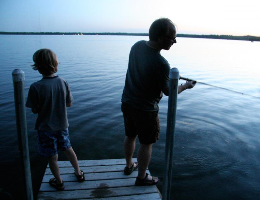 Man and boy fishing from end of dock on lake
