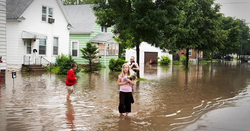 Man holding cat, boy, and girl stand in flooded street in front of homes.