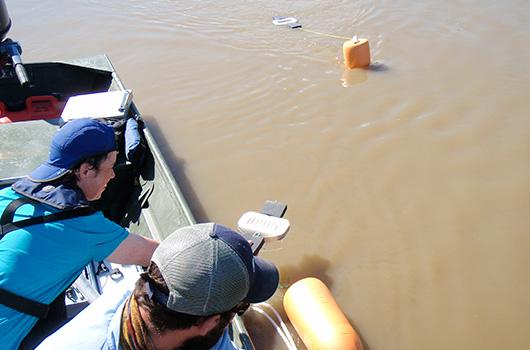 Joy Kennedy and Nate Sather deploy floating sampler in Red River