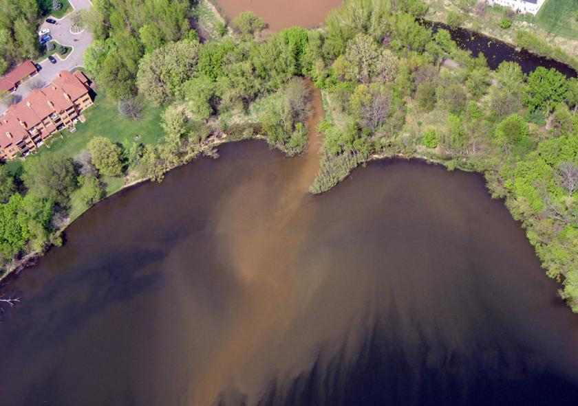 Light brown colored sediment flowing into dark brown lake