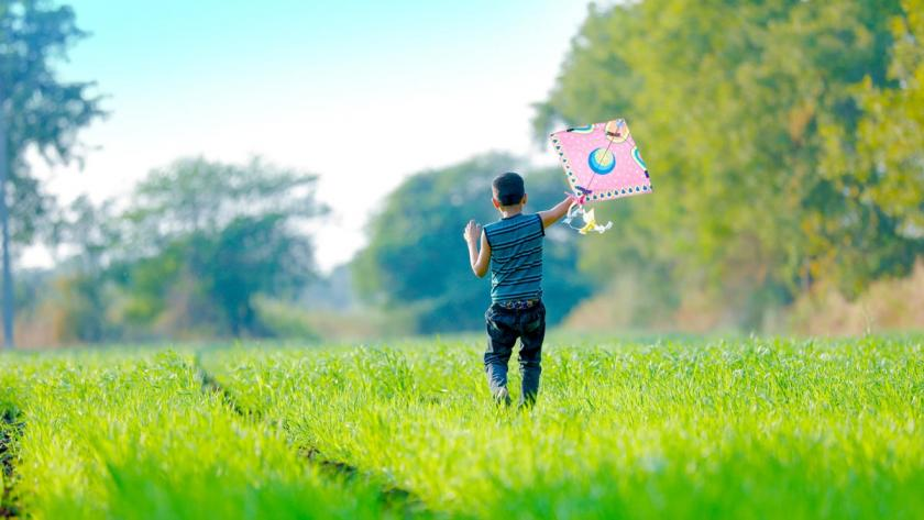 Air we breathe report cover showing a young boy in a grassy field pulling a kite behind him
