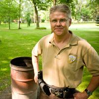 Sheriff standing next to a burn barrel