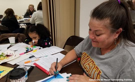 A woman sits at a table and writes on a piece of paper as a nearby child colors with markers.