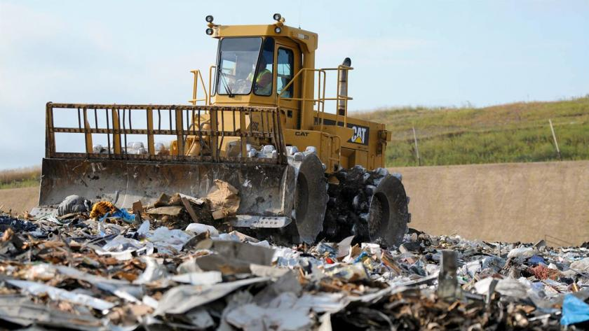 A yellow landfill compactor drives over trash in a landfill.