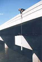 Collecting a grab sample of river water from a bridge
