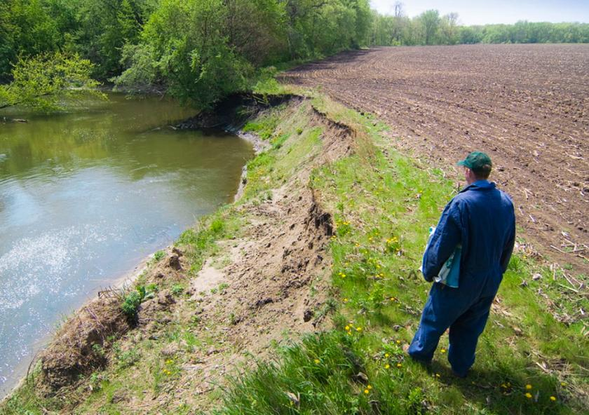 Farmer stands at edge of tilled field looking down a steeply eroded river bank