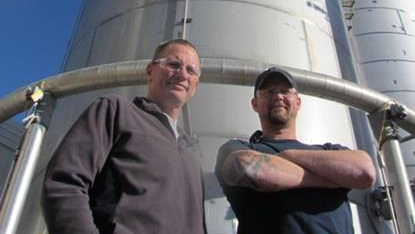 LPI employees Tom Murphy and Jesse Moore pose proudly in front of the company's award-winning effluent treatment plant.