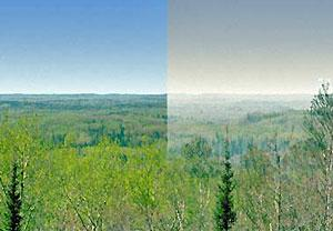 Split view from the Boundary Water Canoe Area Wilderness visibility monitor. The left side shows blue sky and green hills on good days. The right side shows a gray sky and hazy horizon on poor visibility days.