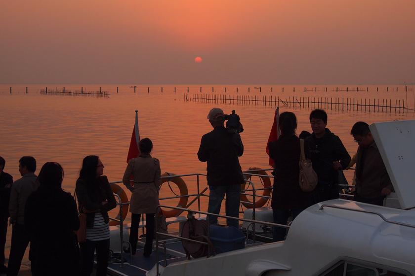 Silhouettes of people on boat looking at hazy orange sunset over Lake Liangzi