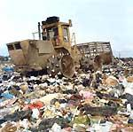 Heavy equipment moving garbage at a landfill