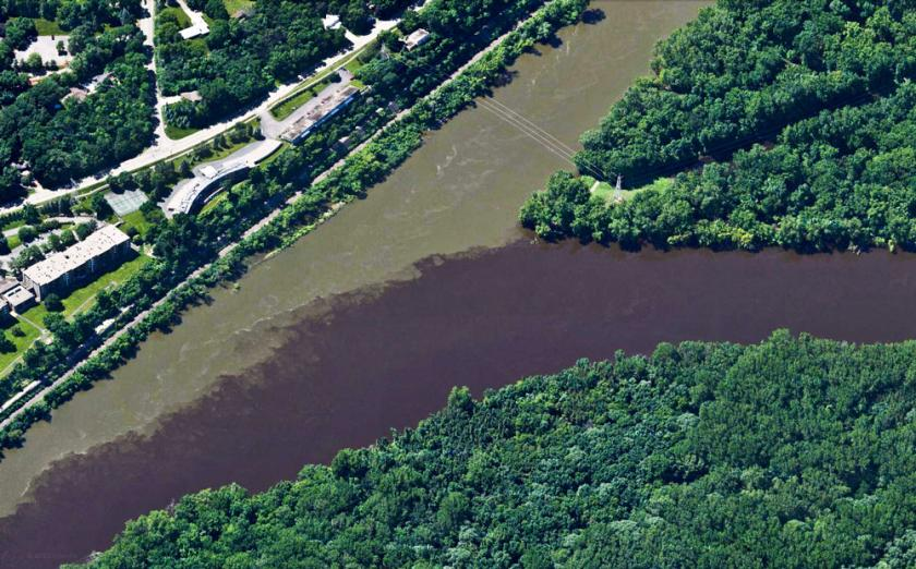 The Minnesota river colored light brown with sediment flows into the dark brown water of the Mississippi river