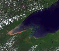 As seen from space, sediment clouded Lake Superior along its shoreline after heavy rains flushed dirt, bacteria and other pollutants into the lake June 19-20. In similar fashion, heavy rains can wash sediment into rivers in southern and western Minnesota.