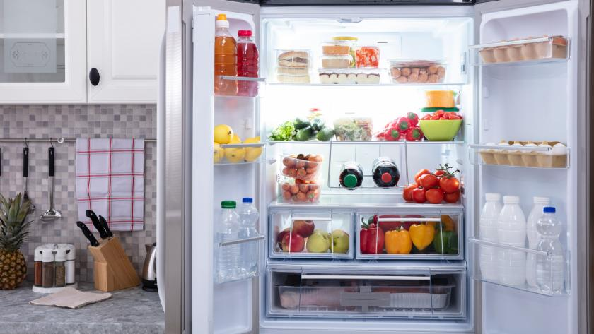 A refrigerator full of food with both doors standing open.
