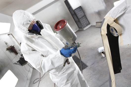 Spraying paint in auto body shop.