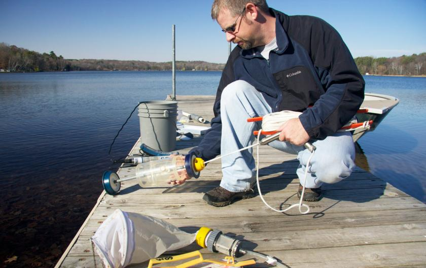 Man kneels on dock putting together water monitoring equipment.