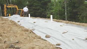 Mound system installation; geotextile fabric and inspection pipes visible.