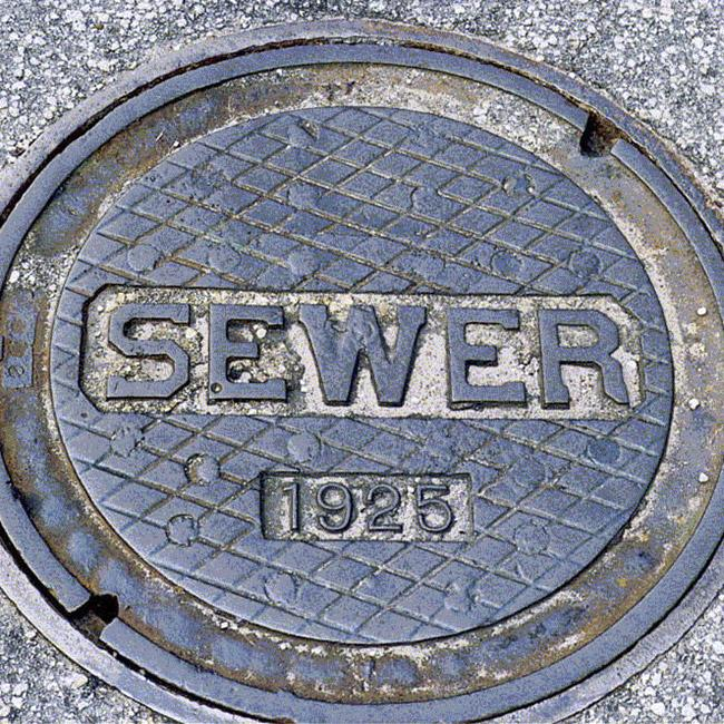 "A waste water manhole cover with the imprinted words ""sewer 1925"""