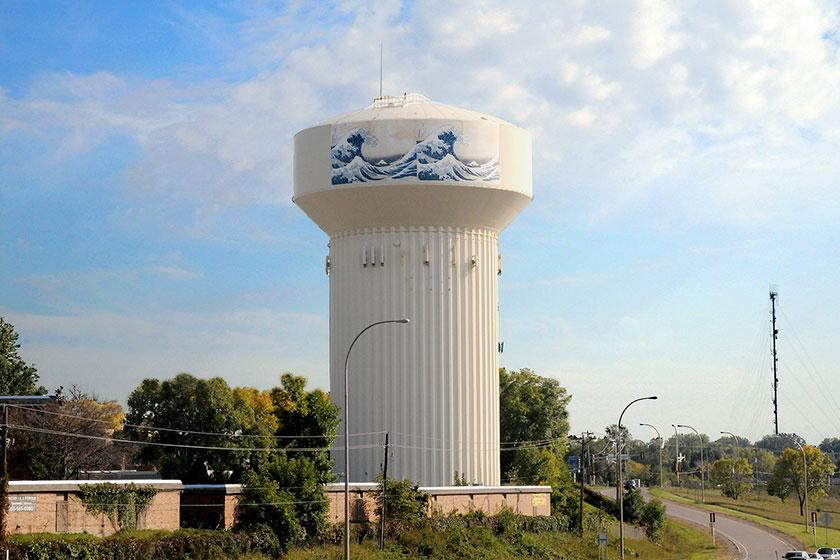 white watertower with wave artwork