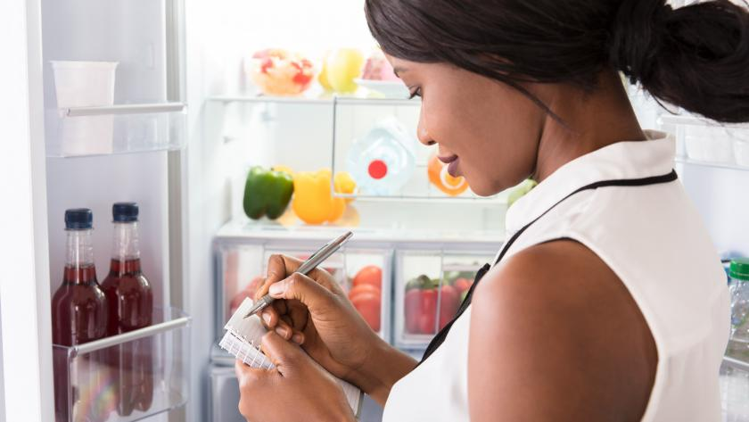 A woman stands in front of an open refrigerator with a notebook and pen to make a list.