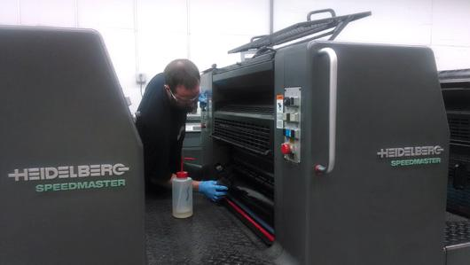 worker-cleaning-commercial-printer