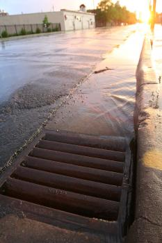 Water from rainfall flowing along gutter to storm drain