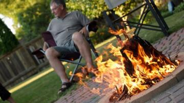 Man sitting next to backyard fire