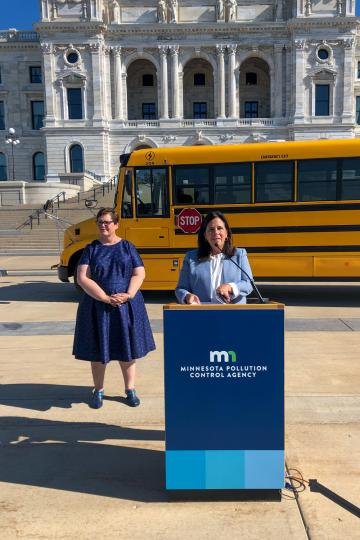 Commissioner Laura Bishop makes an announcement in front of a school bus with the Minnesota State Capitol building in the background.