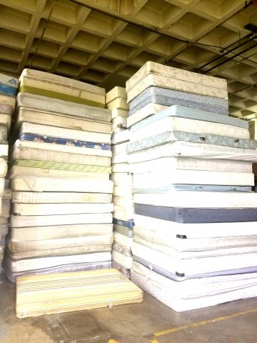 stack of mattresses ready to be disassembled and recycled