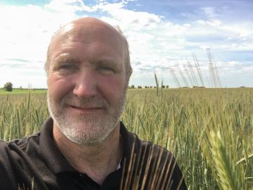 Close up of a man standing in a field of grain.