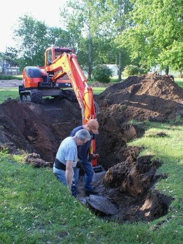 Two men standing in hole in yard looking at cover of septic tank.