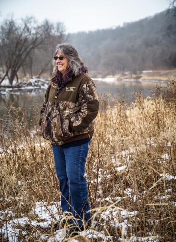 Woman wearing dark glasses, brown jacket and blue jeans stands in dried grass and patches of snow on riverbank, looking off to the distance and smiling.