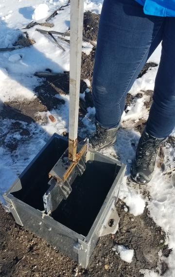 A metal rod lifts up a board that has been inserted into a metal box in the ground