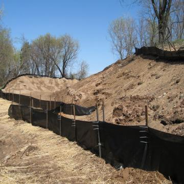 Black plastic barriers prevent soil from washing away from slopes