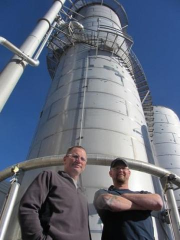 LPI employees Tom Murphy and Jesse Moore pose in front of the company's award-winning effluent treatment plant.