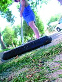 Woman sweeping grass clippings on sidewalk
