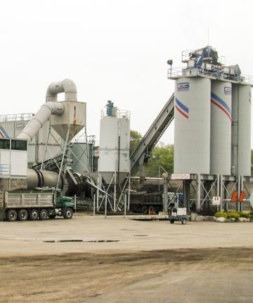 A conveyor belt leads up to three tall grey cylinders at an asphalt mixing plant.