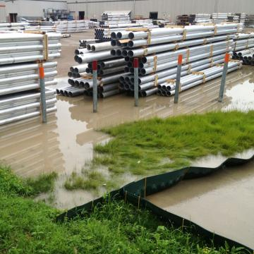 Stacks of long metal pipes in standing storm water runoff