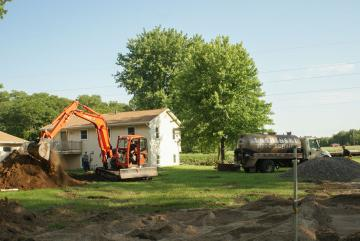 Orange backhoe digs hole in yard behind house for septic tank.